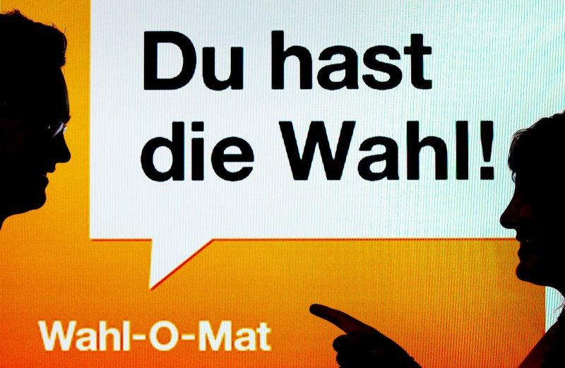 """ARCHIV - ILLUSTRATION - Zwei junge Leute stehen am 22.08.2013 in München (Bayern) vor einen Bildschirm mit der Aufschrift «Du hast die Wahl! - Wahl-O-Mat». (Zu dpa """"Musik, Wahl-«Tinder», Navi: Das sind die Apps zur Bundestagswahl"""" vom 29.08.2017) (© Foto: dpa)"""
